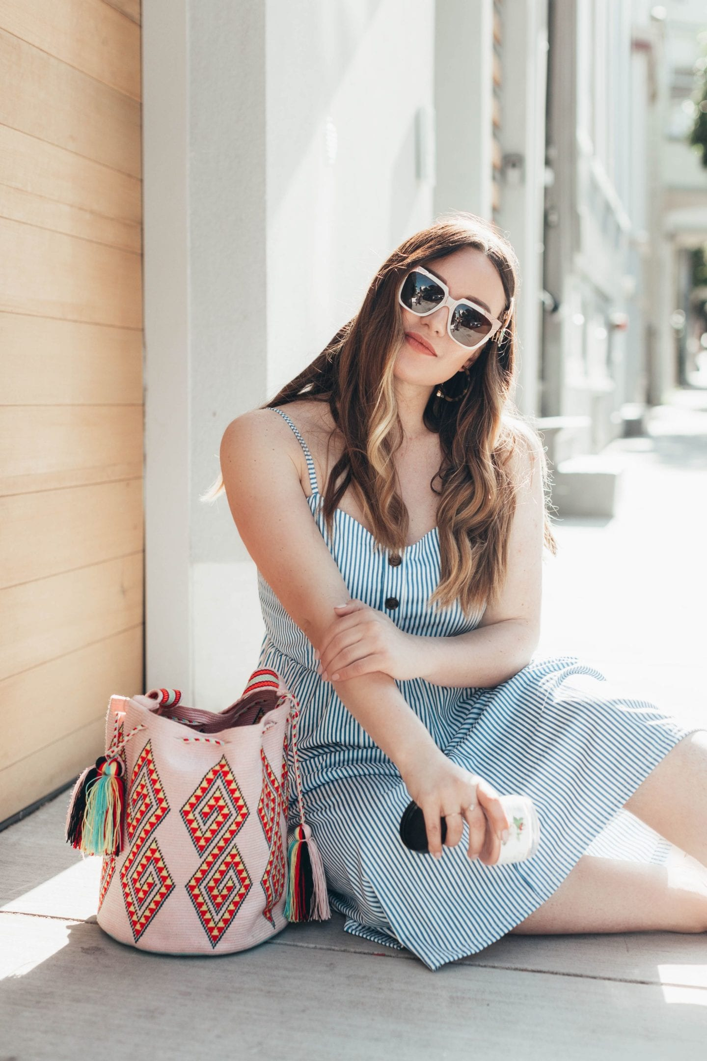 Nourish Organics Products featured by top US beauty blog Just Add Glam; Image of a woman wearing a blue striped sundress and sunglasses.