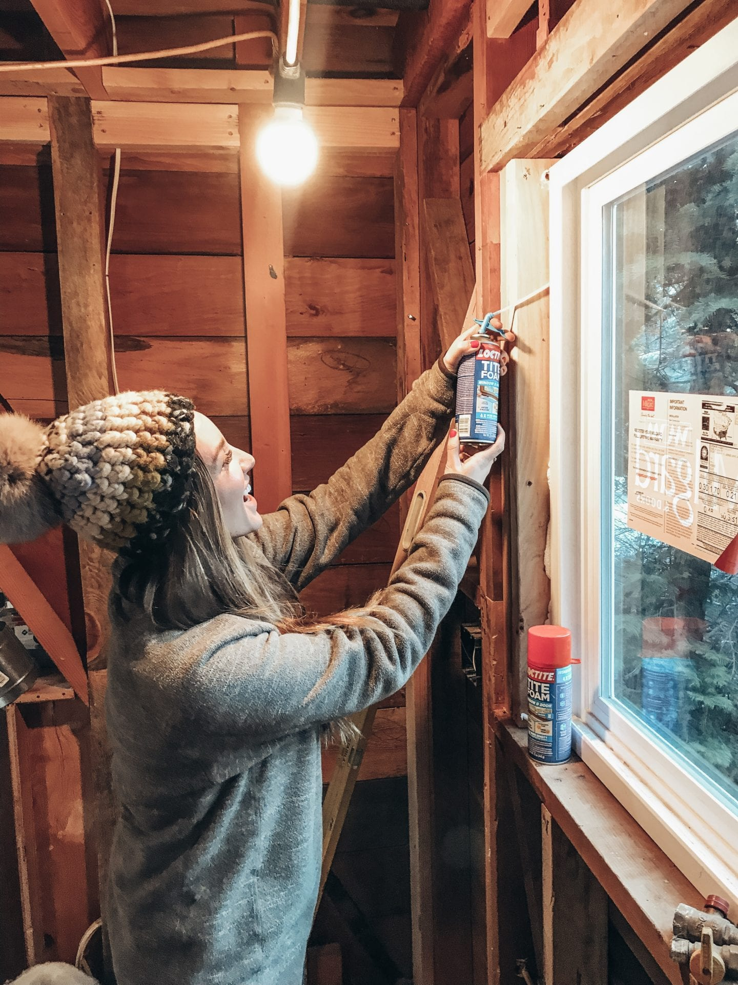 How To Winterize Windows featured by top US lifestyle blog Just Add Glam; Image of a woman fixing window.