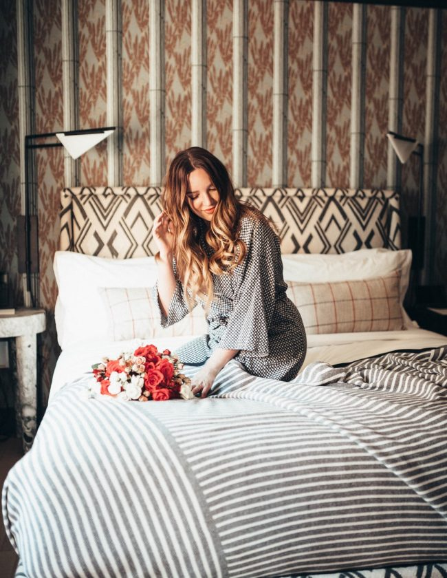 How To Have a Stress-Free Valentine's Day featured by top US life and style blog, Just Add Glam: image of a woman on her bed with a romantic bouquet in her hands