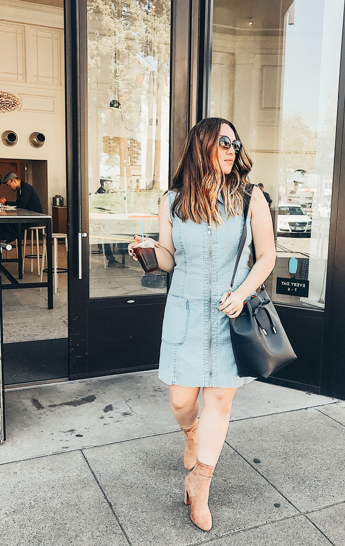 Top 10 Cute Denim Dresses for Summer I Summer Fashion I Fashion Blog I via justaddglam.com | Top 10 Cute Denim Dresses for Summer by popular San Francisco fashion blog, Just Add Glam: image of a woman standing outside in front of a restaurant wearing a sleeveless denim dress and tan suede ankle boots.