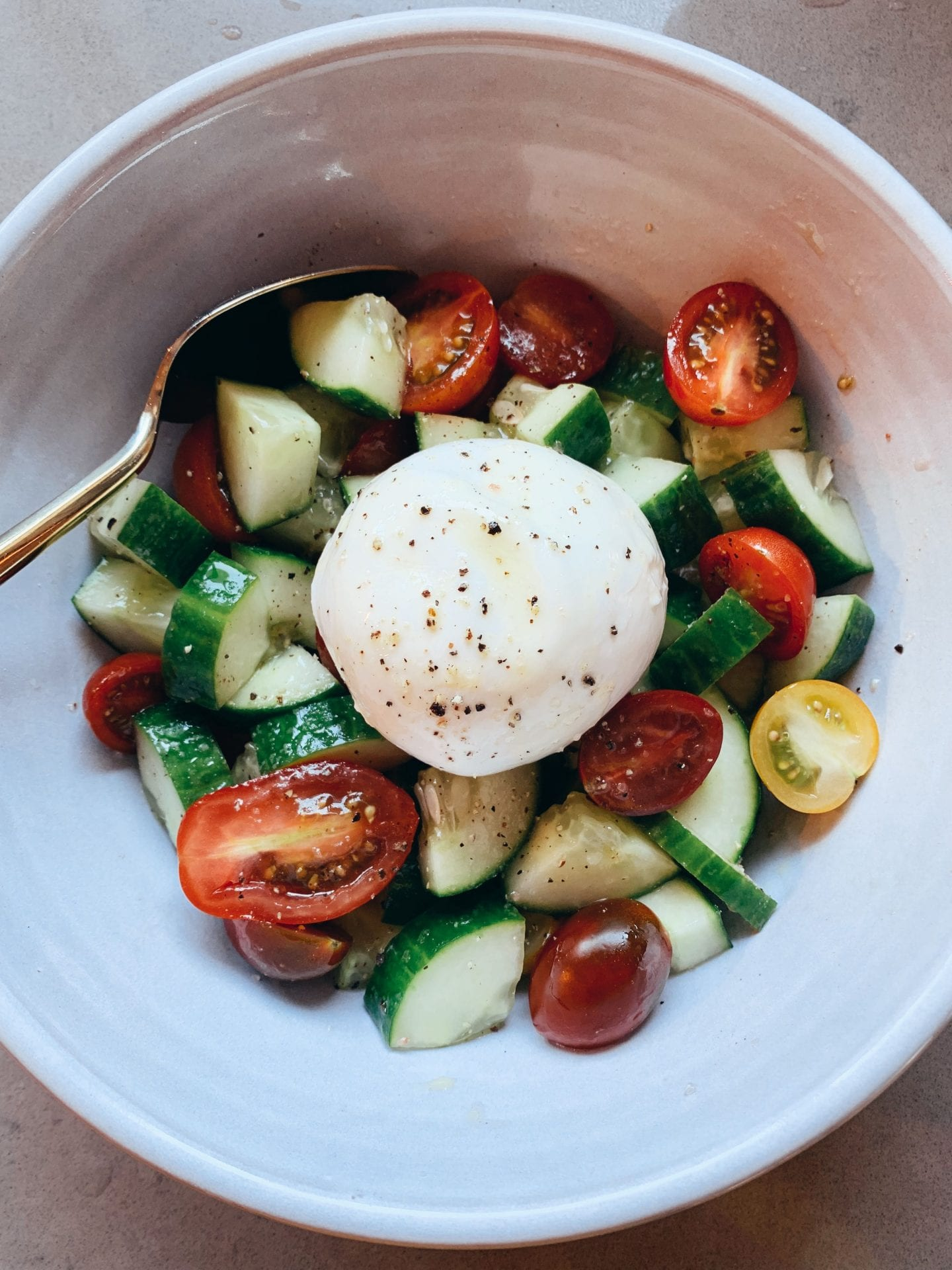 Fresh Cucumber Tomato Burrata Salad Recipe I Keto Recipe I Kept Cooking I Summer Recipe I via justaddglam.com |Fresh Cucumber Tomato Burrata Salad Recipe--Keto Friendly! by popular life and style blog, Just Add Glam: image of some burrata salad in a white ceramic bowl with a gold spoon.