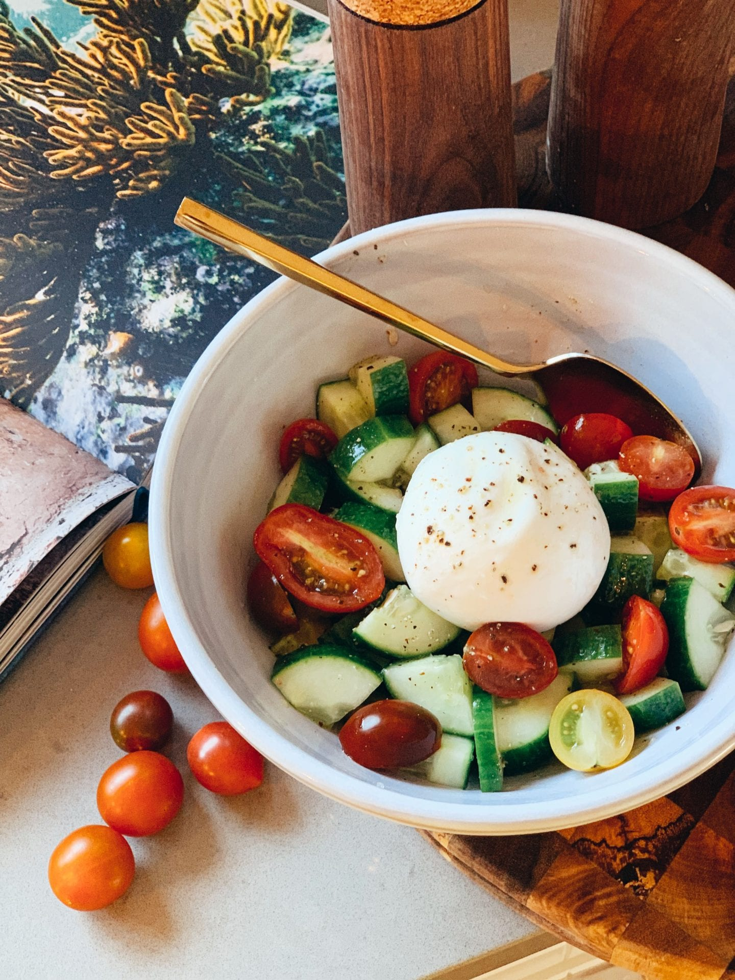 Fresh Cucumber Tomato Burrata Salad Recipe--Keto Friendly! by popular life and style blog, Just Add Glam: image of some burrata salad in a white ceramic bowl with a gold spoon.