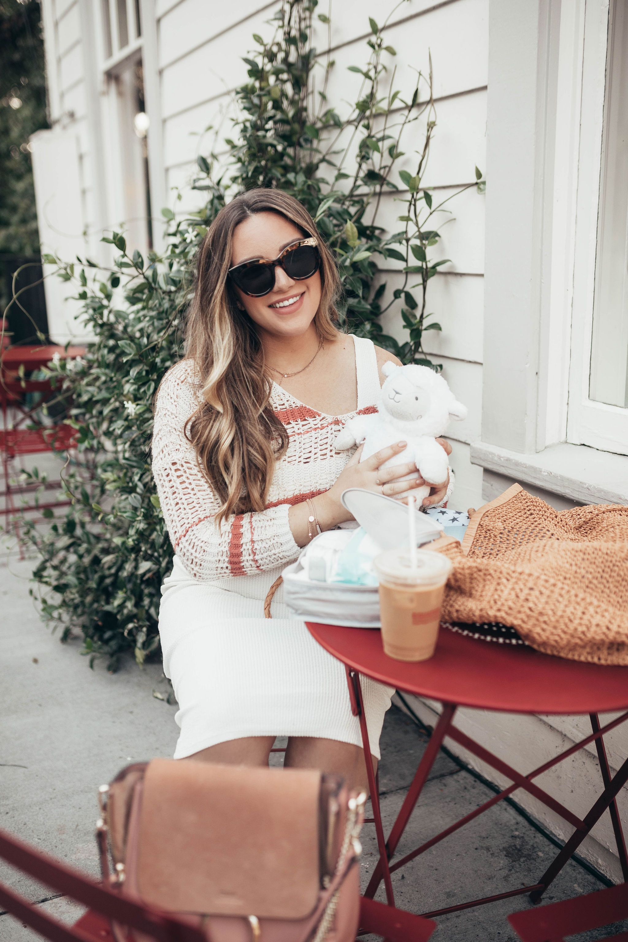 25 Bestseller Walmart Baby Products by popular San Francisco life and style blog, Just Add Glam: image of a woman sitting at a cafe table outside with an iced coffee, Walmart Mustela newborn arrival gift set, and other various Walmart baby products.
