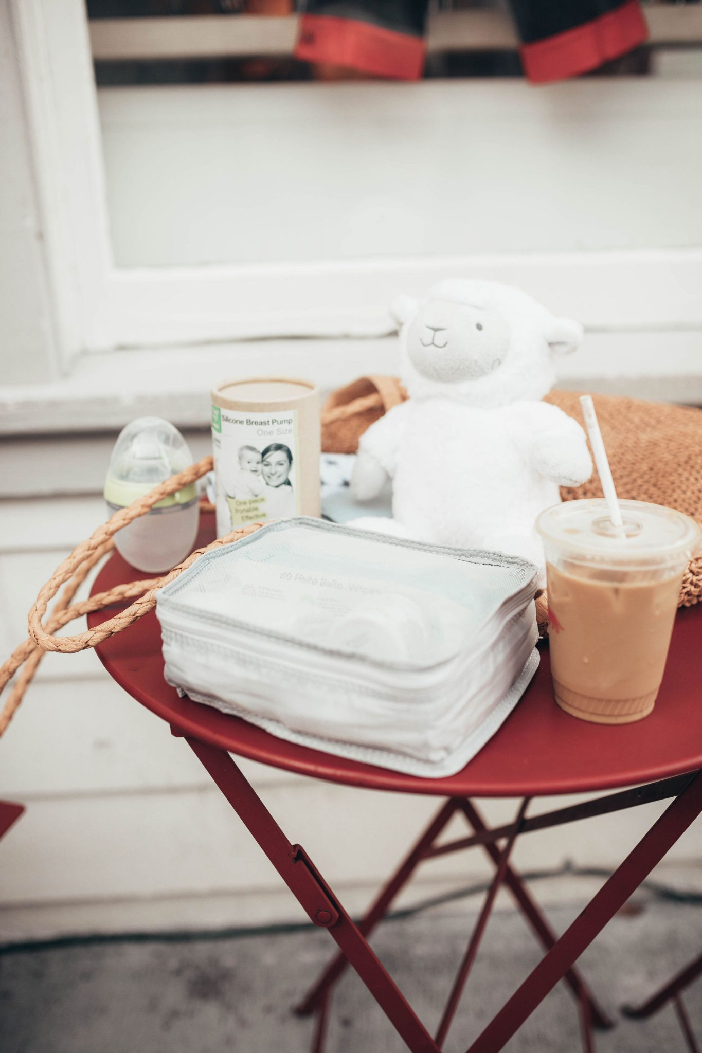 25 Bestseller Walmart Baby Products by popular San Francisco life and style blog, Just Add Glam: image of a woman sitting at a cafe table outside with an iced coffee and various Walmart baby products.