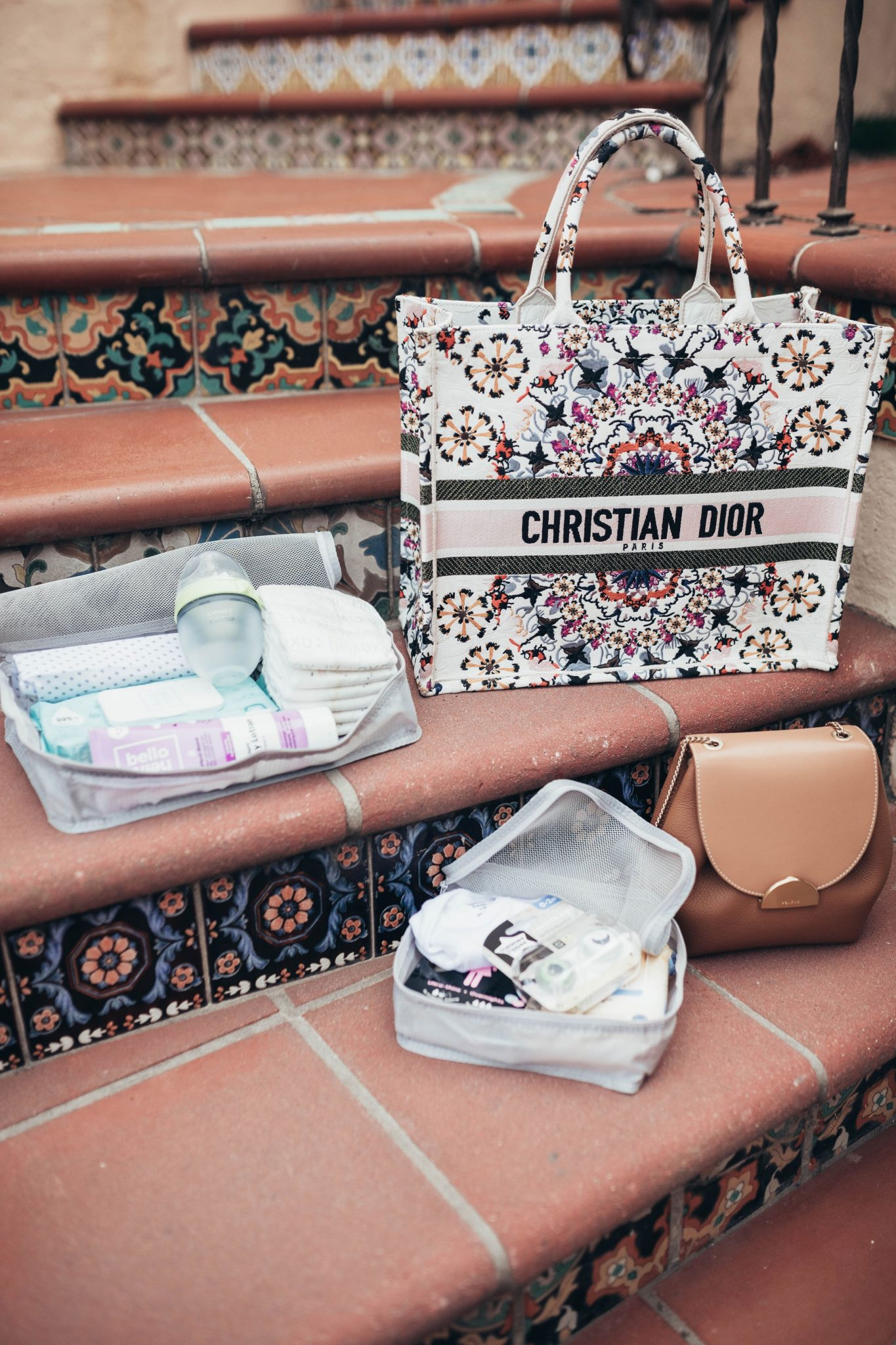 Top Deals On Must-Have Baby Essentials From Walmart by popular San Francisco life and style blog, Just Add Glam: image of a Christian Dior bag and various Walmart baby products on some steps.