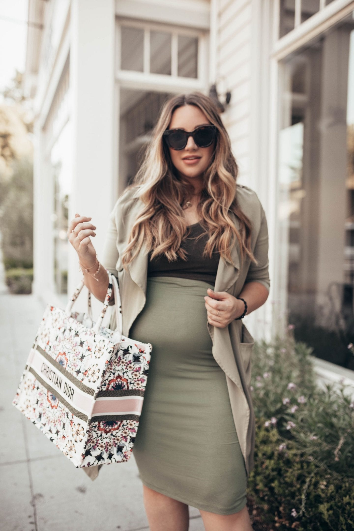 Maternity Style for Each Trimester by popular California fashion blog, Just Add Glam: image of a woman wearing a olive green high waist skirt, black shirt, and green sweater jacket.