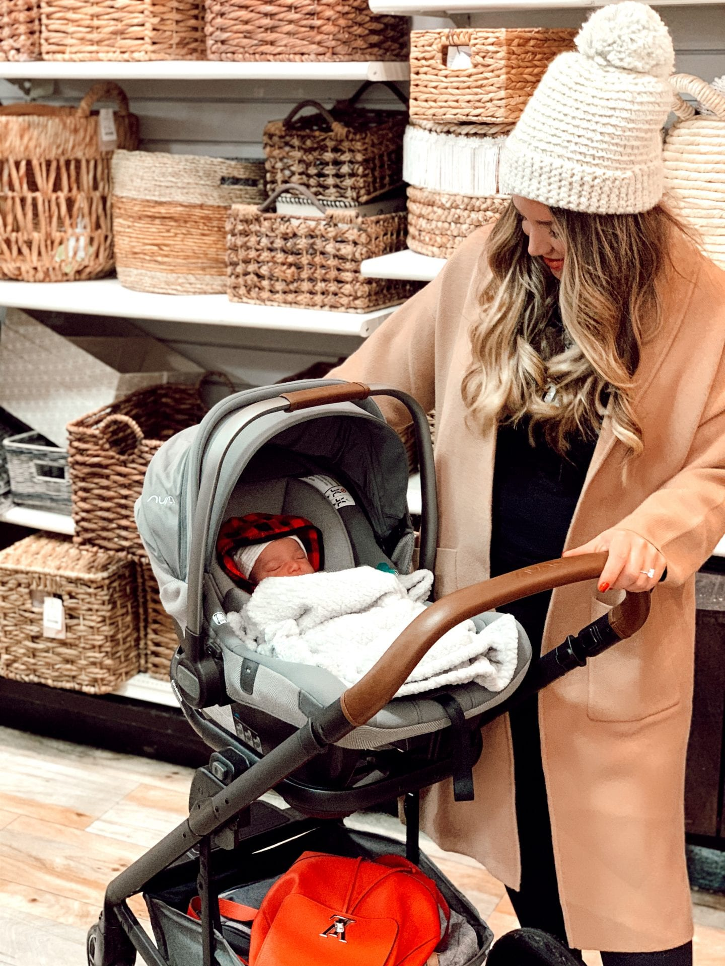 camel coat 2020 | 12 BEST CAMEL COATS FOR 2020 by popular California fashion blog, Just Add Glam: image of a woman pushing her baby in a stroller and wearing a camel coat.
