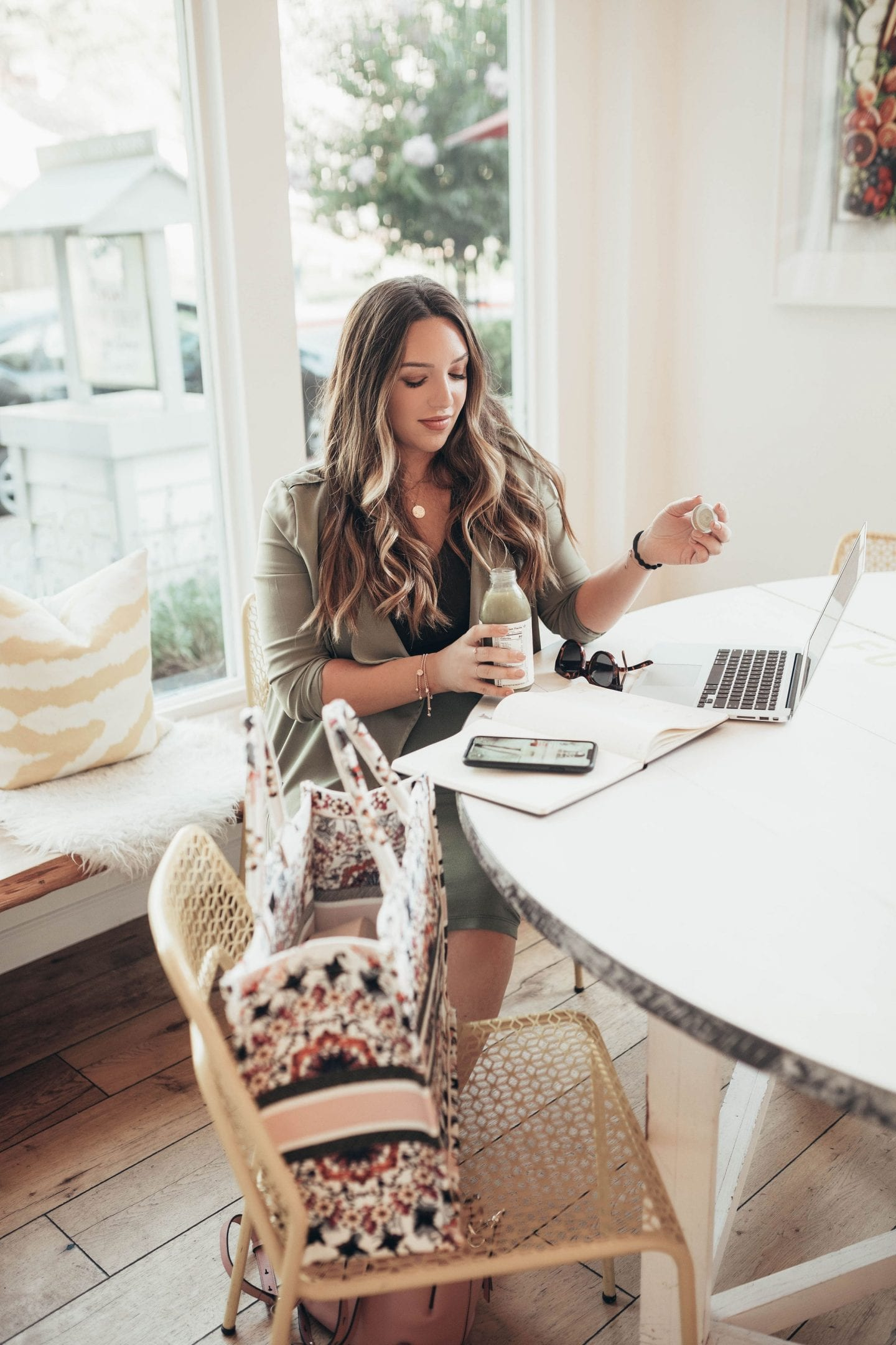 Best Motivational Podcasts by popular San Francisco lifestyle blog, Just Add Glam: image of a woman sitting at a table with her laptop, notebook, and her smartphone.
