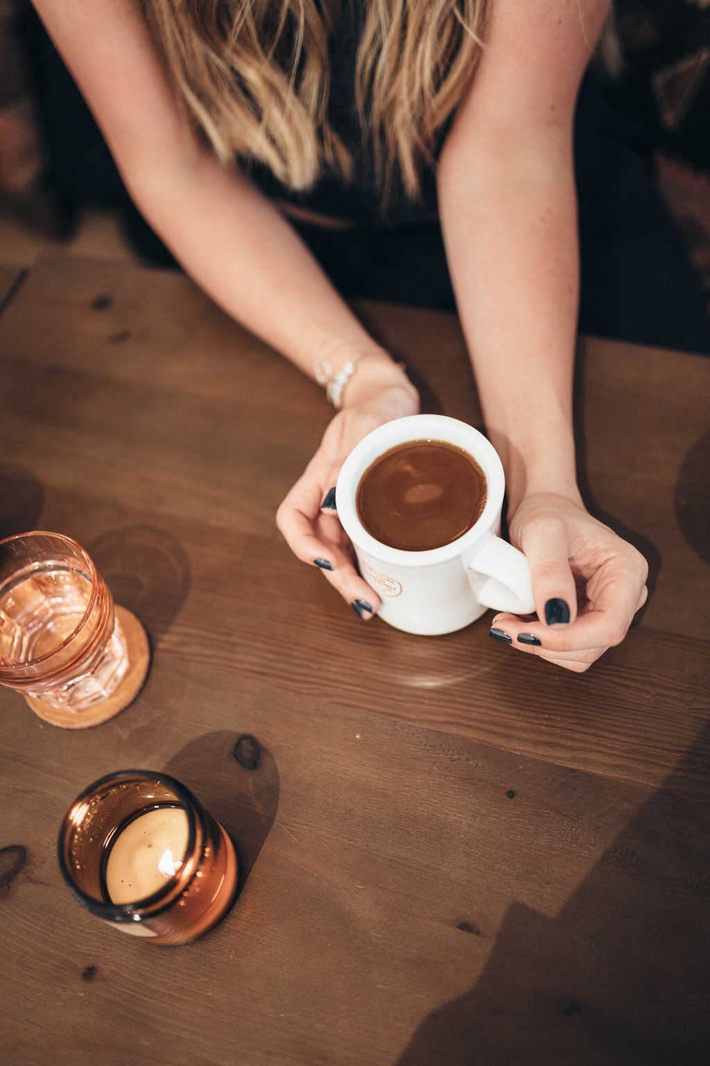 ditching starbucks habit | WHY I'M DITCHING MY STARBUCKS ADDICTION AND HOW YOU CAN TOO by popular San Francisco life and style blog, Just Add Glam: image of a woman sitting at a table and holding a coffee cup.