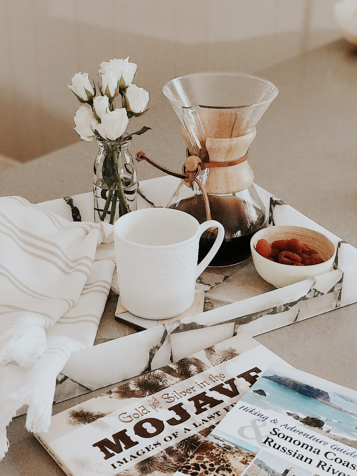 HOW TO STOP WASTING FOOD AND GROCERIES AND SAVE MONEY by popular San Francisco lifestyle blog, Just Add Glam: image of a marble breakfast tray with a carafe of coffee, a white mug, and a small bowl of raspberries on it.