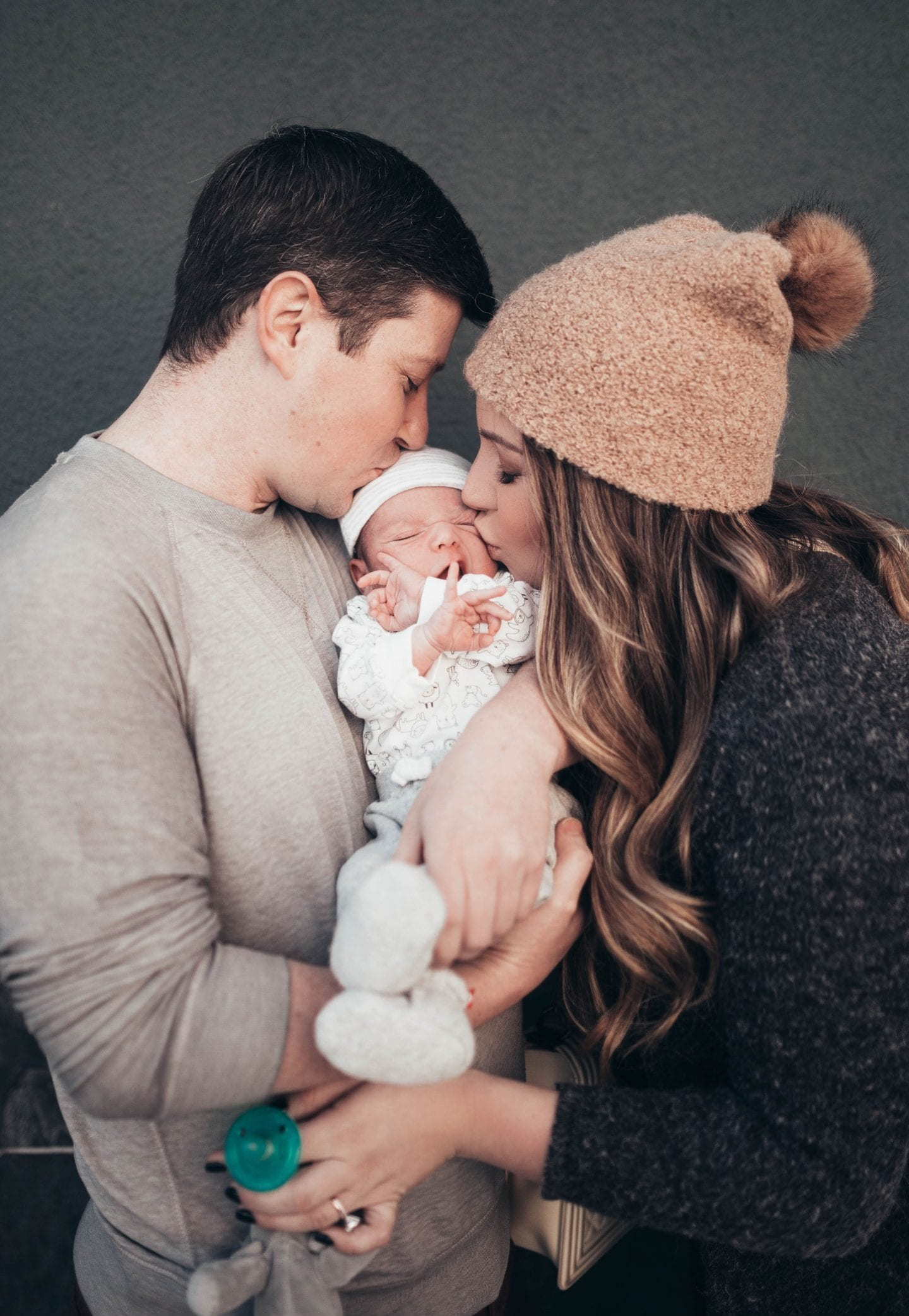 70% Off Carter's Clothing Sale by popular San Francisco lifestyle blog, Just Add Glam: image of a mom and dad holding and kissing their newborn baby.