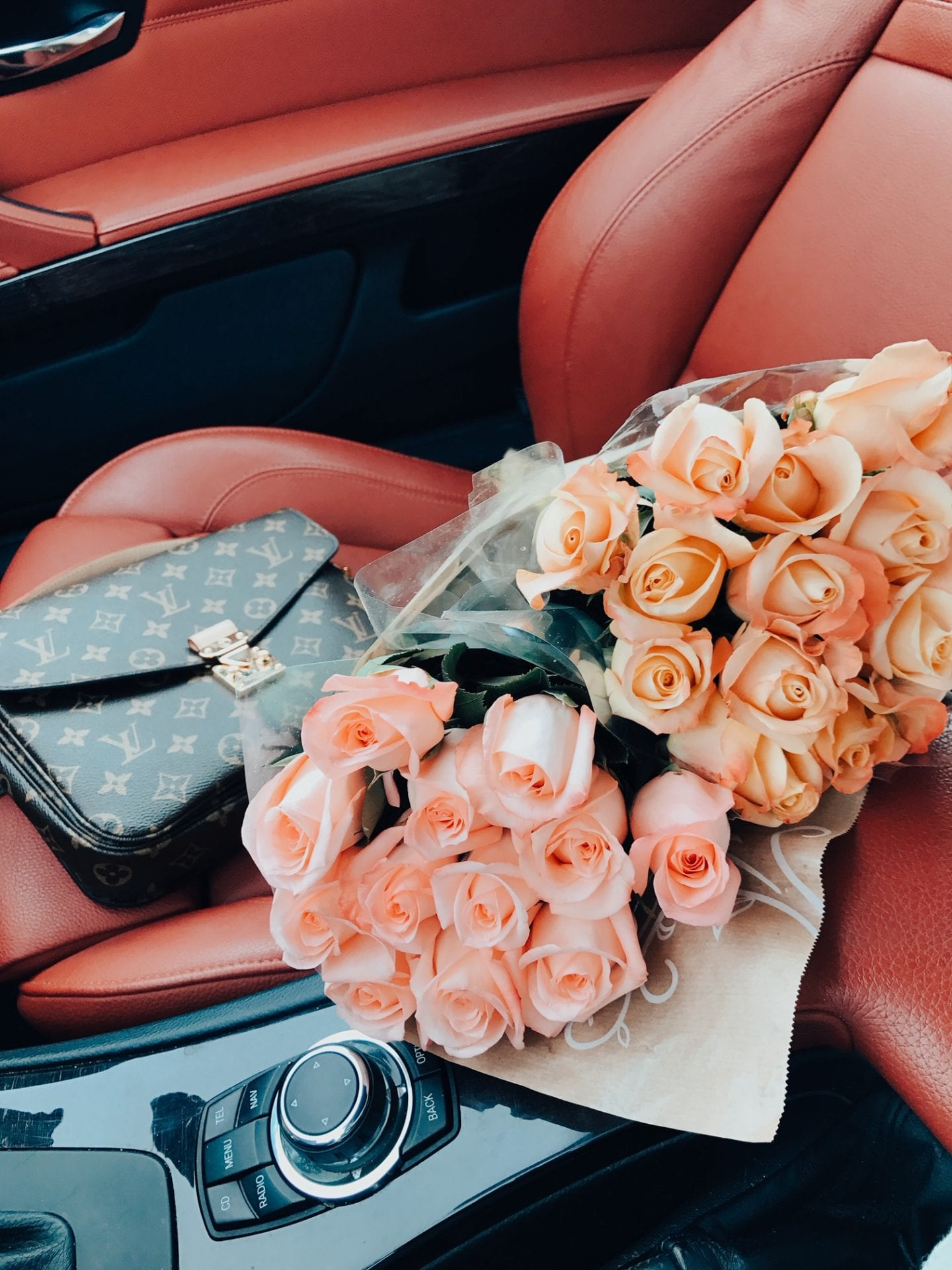 Best Valentine's Day Gifts for Her by popular San Francisco life and style blog, Just Add Glam: image of a Louis Vuitton clutch and pink roses on a red leather car seat.
