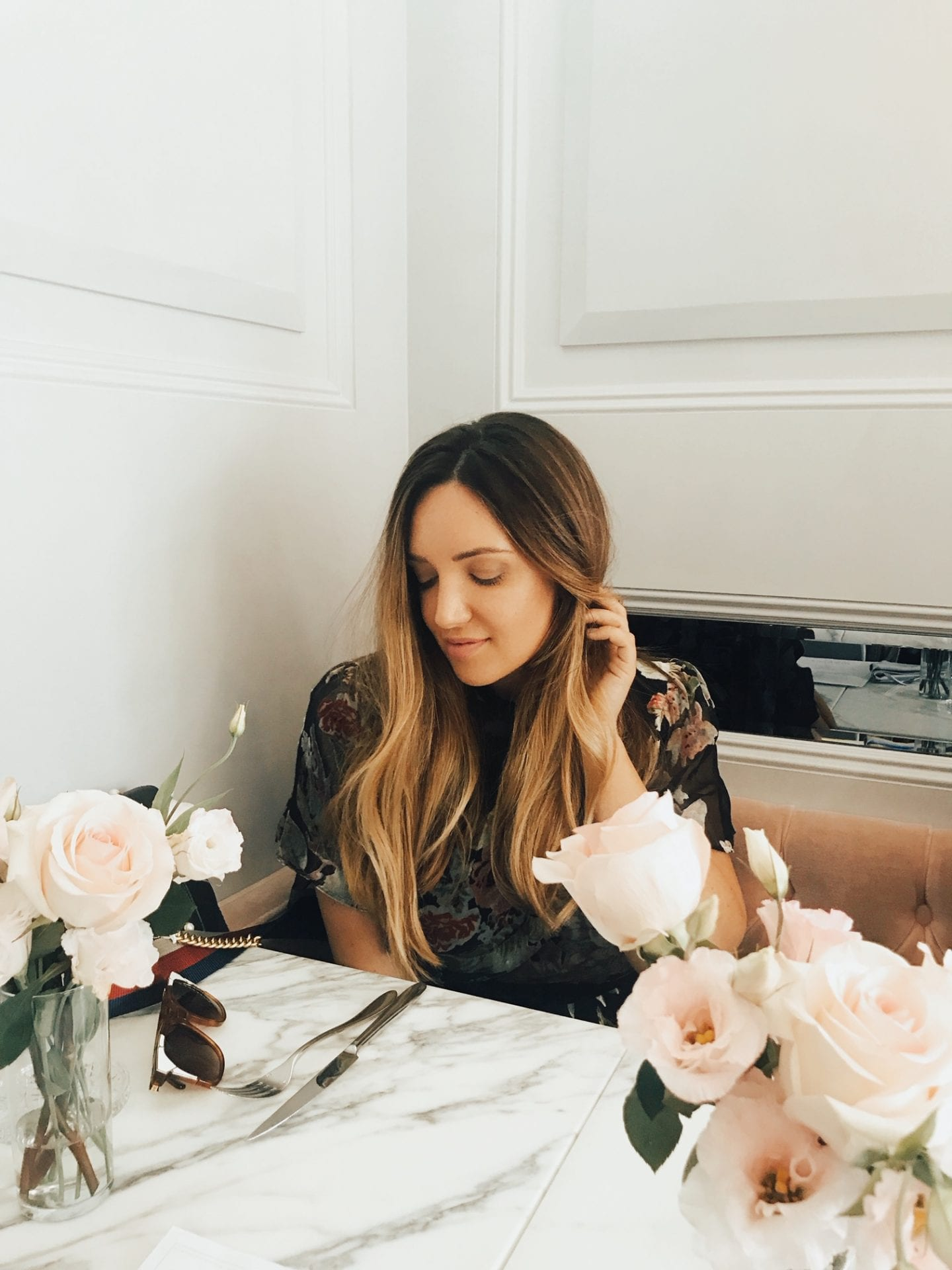 Best Valentine's Day Gifts for Her by popular San Francisco life and style blog, Just Add Glam: image of a woman sitting at a marble table with pink roses on it.