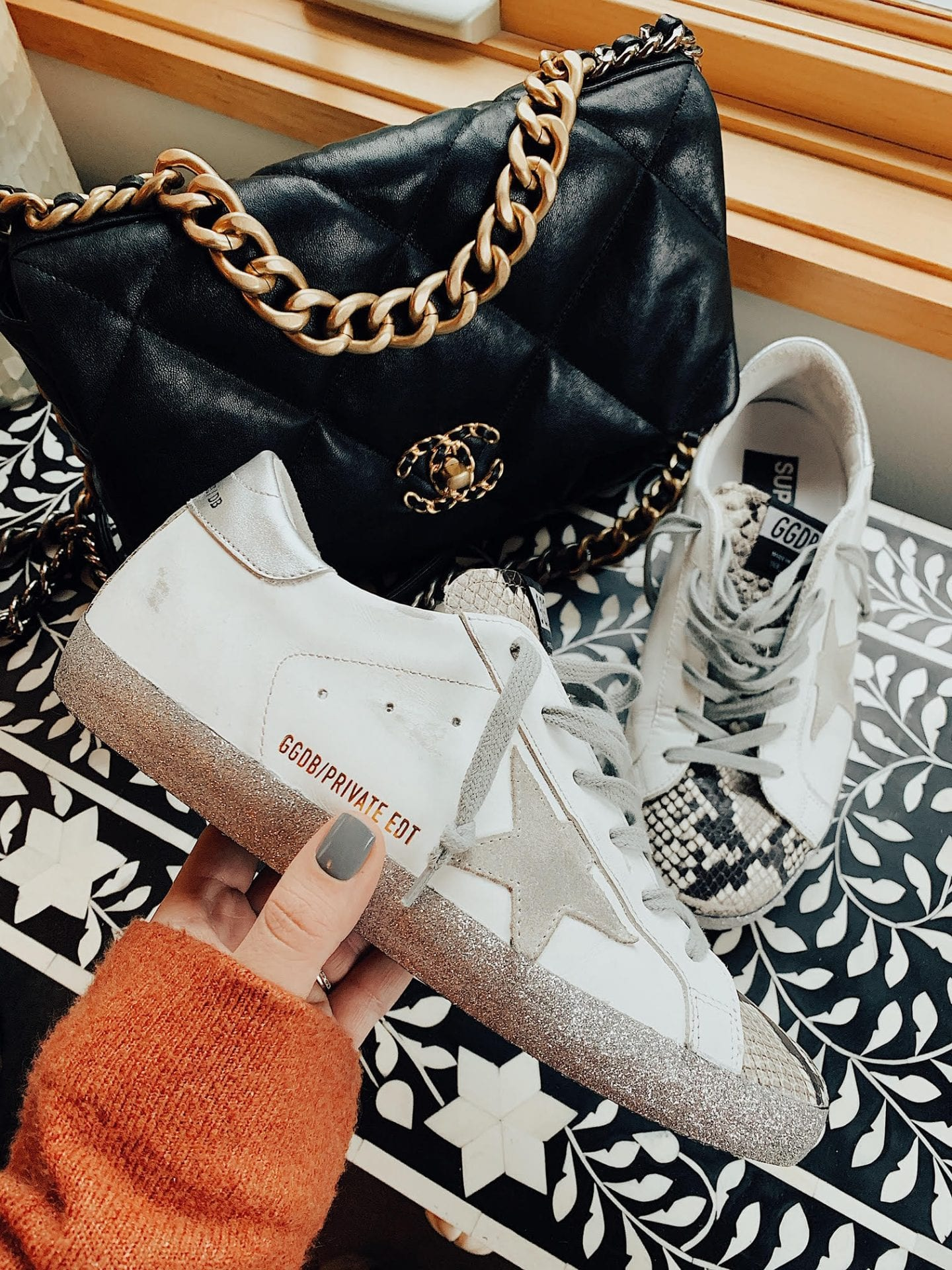 Golden Goose sneakers | Golden Goose Sneakers on Sale by popular San Francisco fashion blog, Just Add Glam: image of a woman holding a golden goose private edition sneaker.