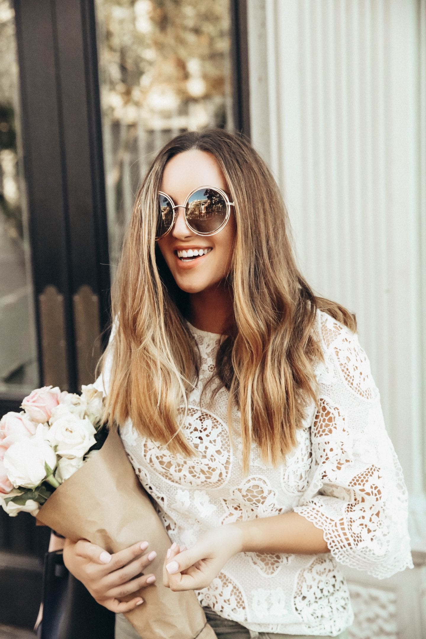 living proof hair | Living Proof Hair Products by popular San Francisco lifestyle blog, Just Add Glam: image of a woman standing outside, holding a bouquet of white and pink roses and running her fingers through her hair.