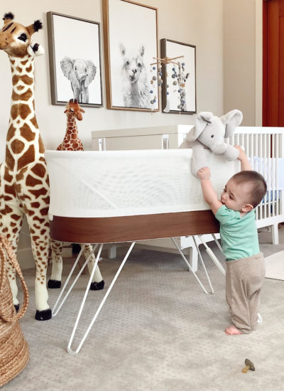 newborn baby products I actually used | Newborn Baby Items by popular San Francisco motherhood blog, Just Add Glam: image of a baby boy standing next to a bassinet and a life size stuffed giraffe.