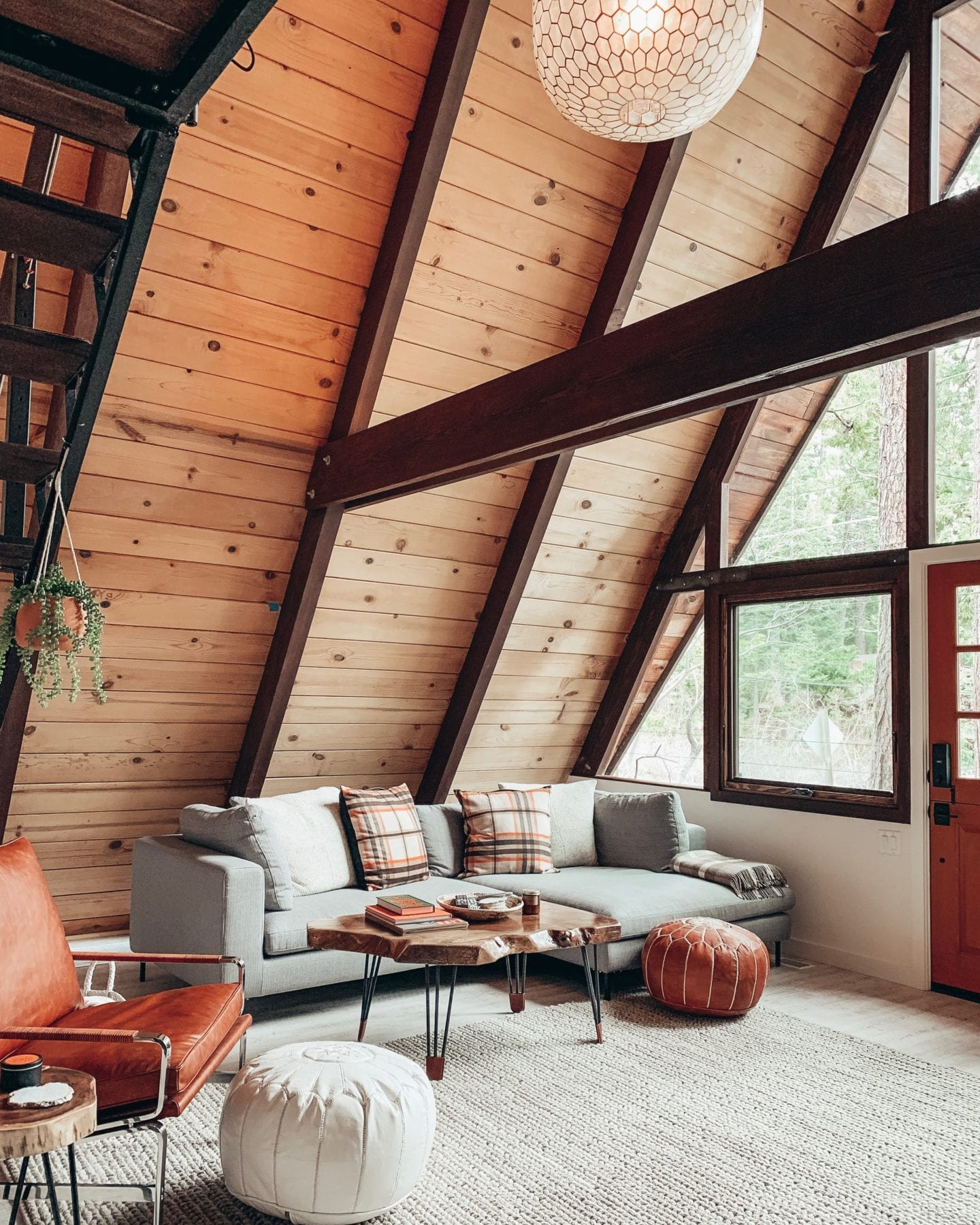 What to Stream on Netflix During Covid 19 by popular San Francisco lifestyle blog, Just Add Glam: image of a A Frame cabin interior with a tan braided rug, leather arm chair, honeycomb pendant light, grey sectional couch, and leather poufs.