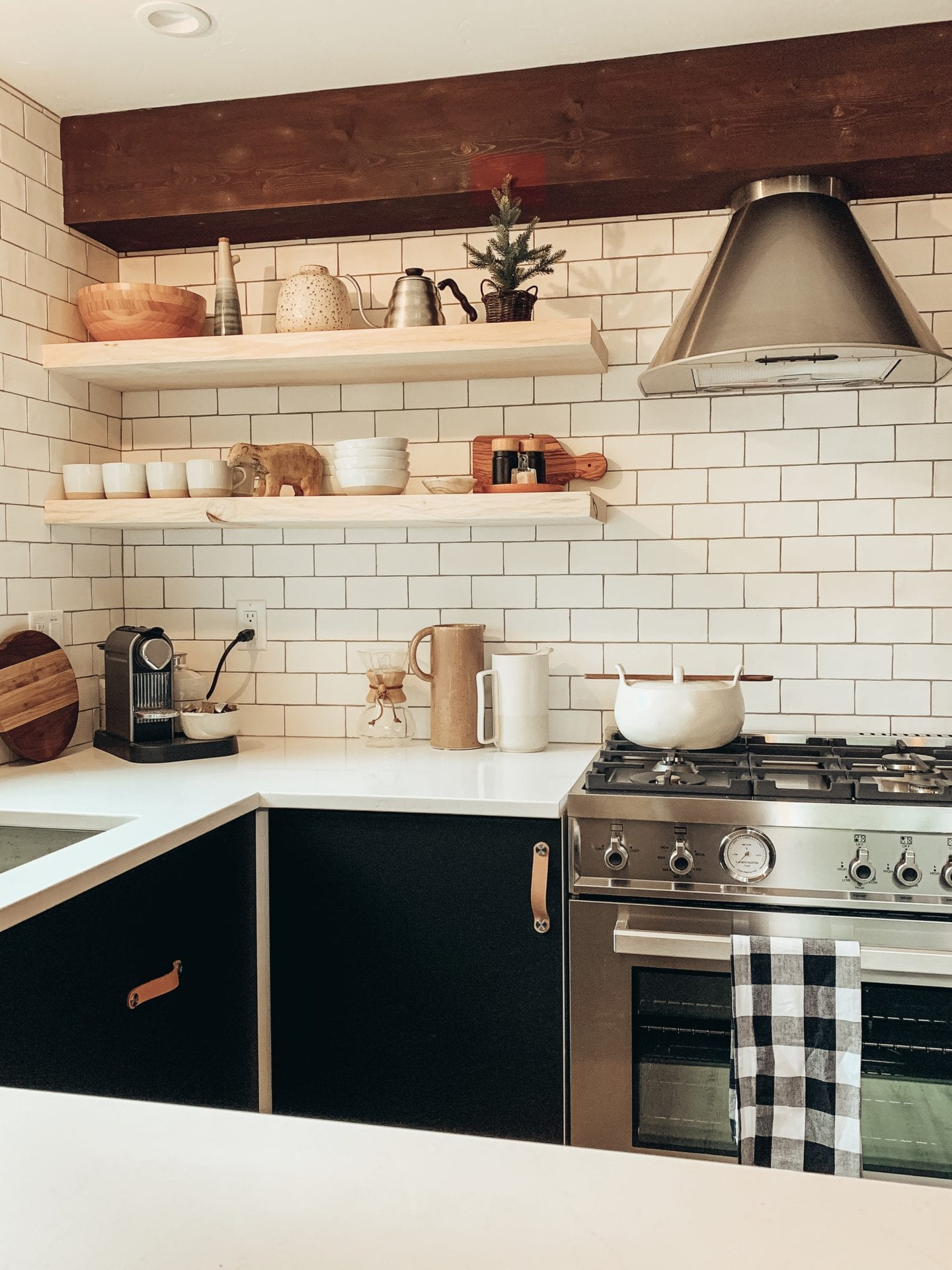Pantry Meals by popular lifestyle blog, Just Add Glam: image of a kitchen with black cabinets, subway title back splash, floating shelves, and gas cooking range.
