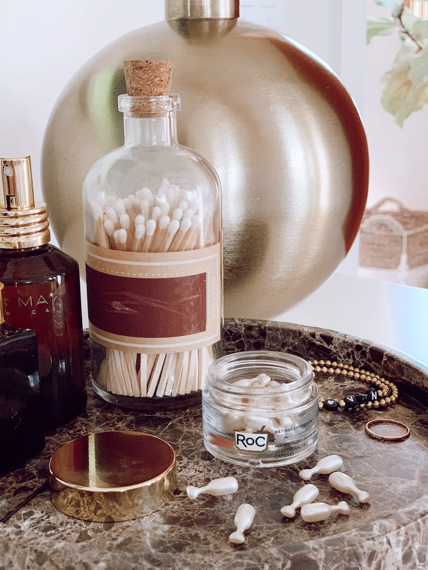 Roc Retinol by popular San Francisco beauty blog, Just Add Glam: image of Roc Retinol capsules on a marble tray next to a jar of q-tips, gold stack bracelets, and a bottle of perfume.