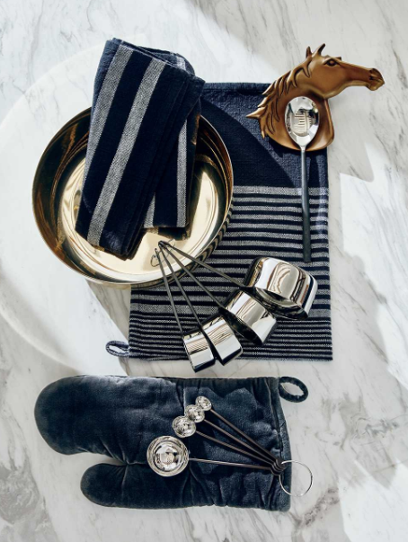 CB2 Home Sale by popular life and style blog, Just Add Glam: image of a blue oven mitt, gold mixing bowl, horse spoon rest, measuring cups, blue and grey strip towel, and measuring spoons.