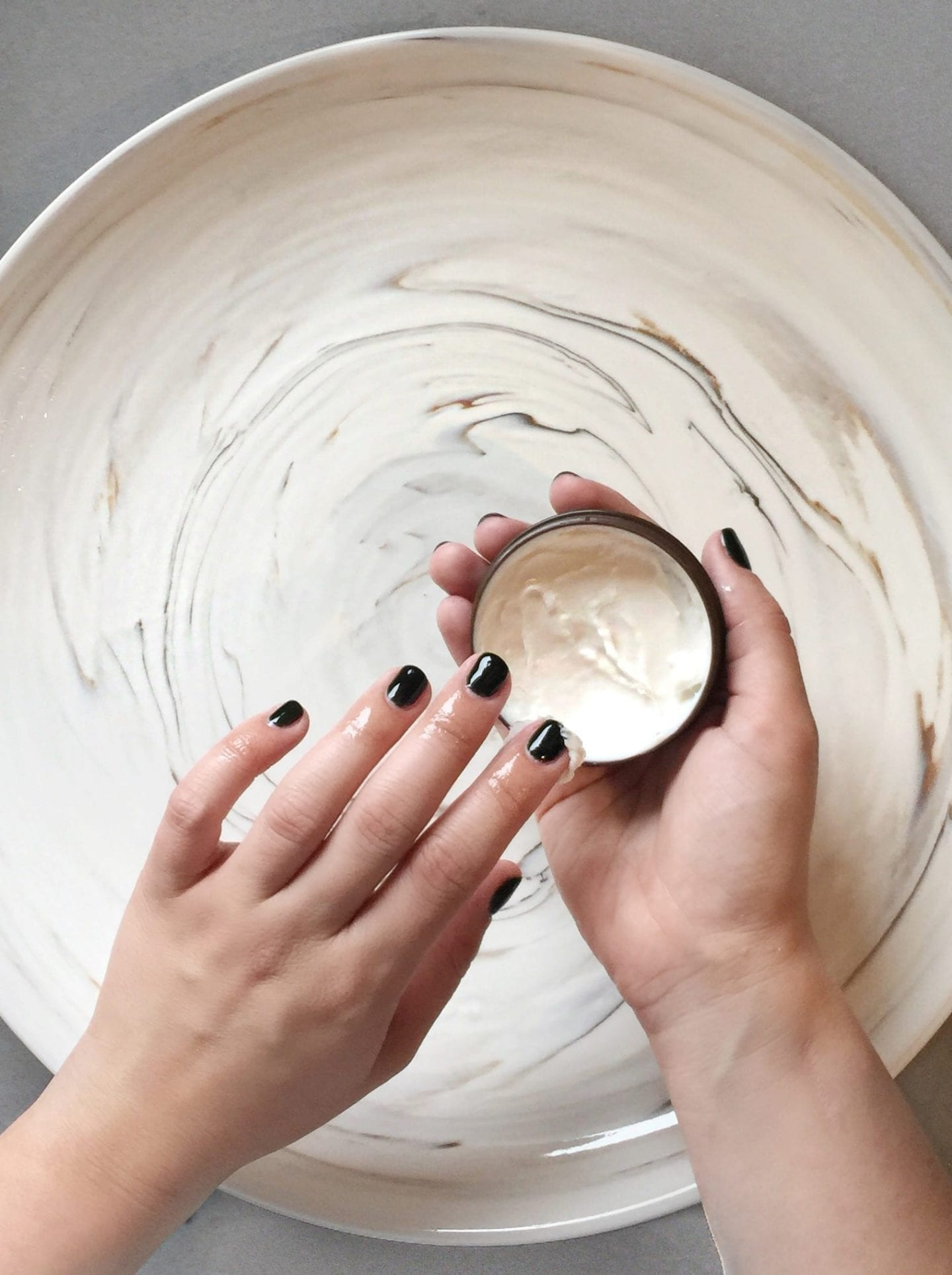 How to Heal Dry Hands by popular San Francisco lifestyle blog, Just Add Glam: image of a woman applying hand cream to her hands.