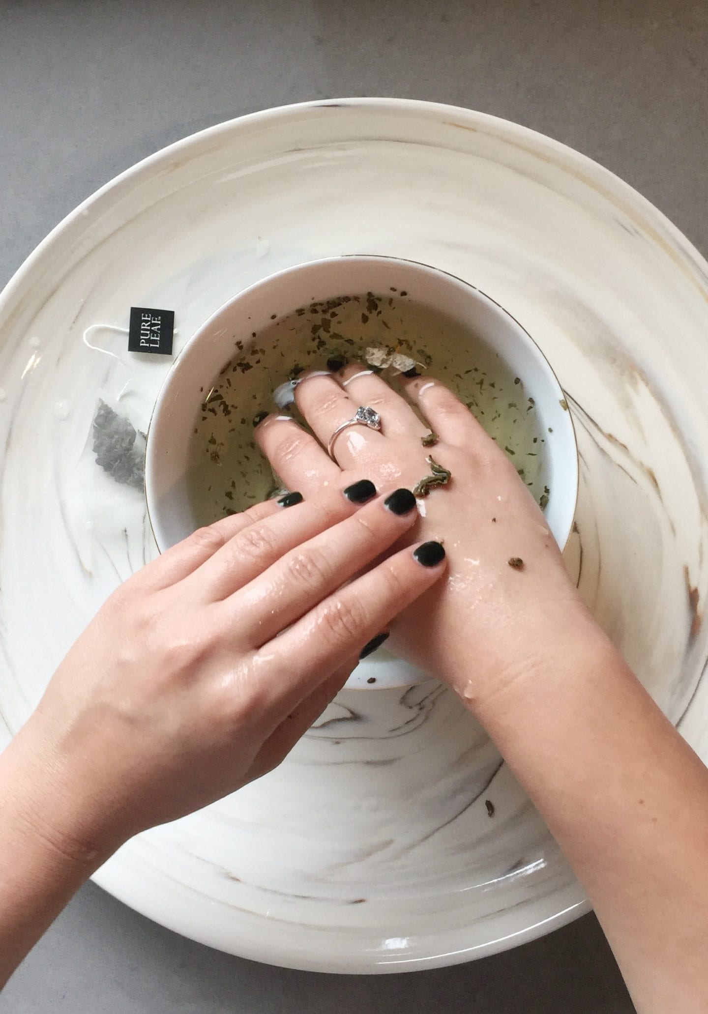 How to Heal Dry Hands by popular San Francisco lifestyle blog, Just Add Glam: image of a woman washing her hands with tea leaves.