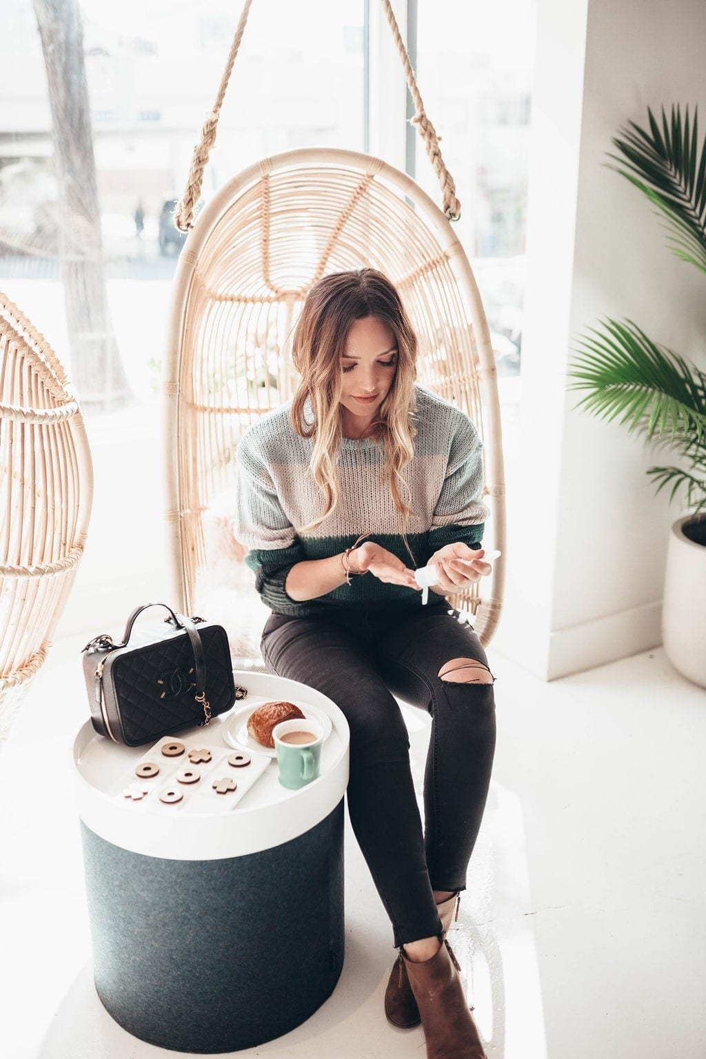 How to Heal Dry Hands by popular San Francisco lifestyle blog, Just Add Glam: image of a woman sitting in a hanging rattan chair and applying lotion to her hands.