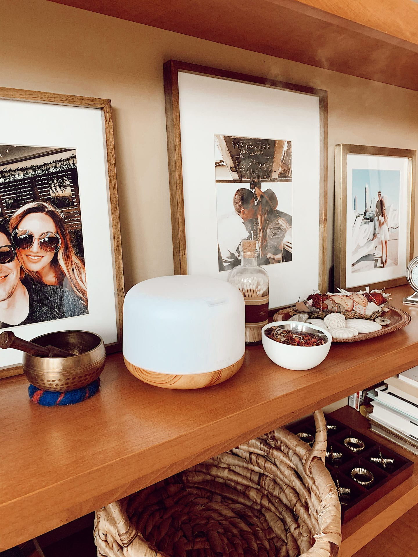 Essential Oil Diffuser Combos by popular San Francisco lifestyle blog, Just Add Glam: image of a essential oil diffusers on a shelf next to framed pictures, a woven basket and a dish full of seashells.