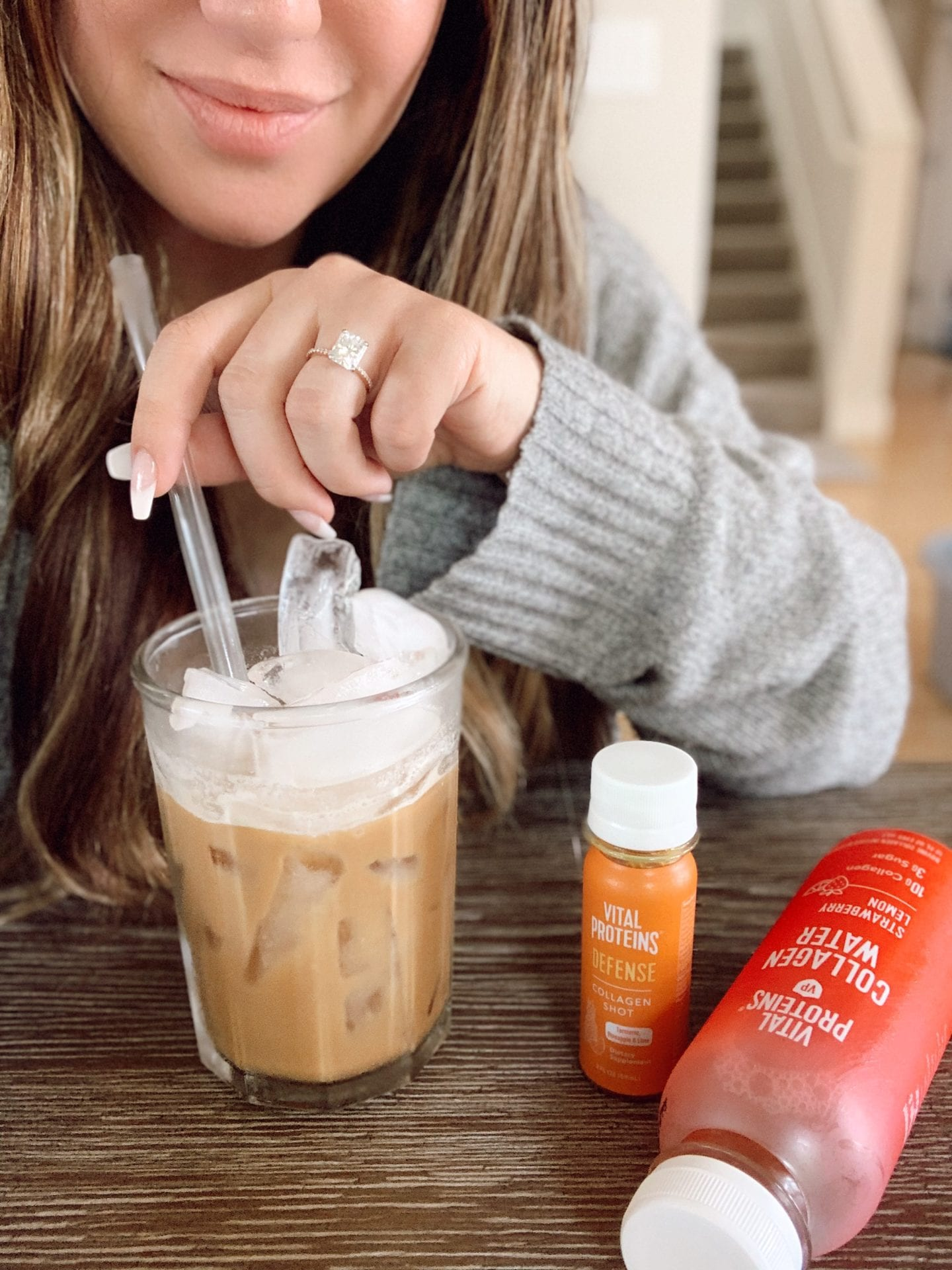 Vital Proteins Collagen Powder | Vital Proteins Collagen Peptides by popular San Francisco beauty blog, Just Add Glam: image of a woman drinking an iced coffee and sitting next to a bottle of Vital Proteins Defense and Vital Proteins Collagen Water.