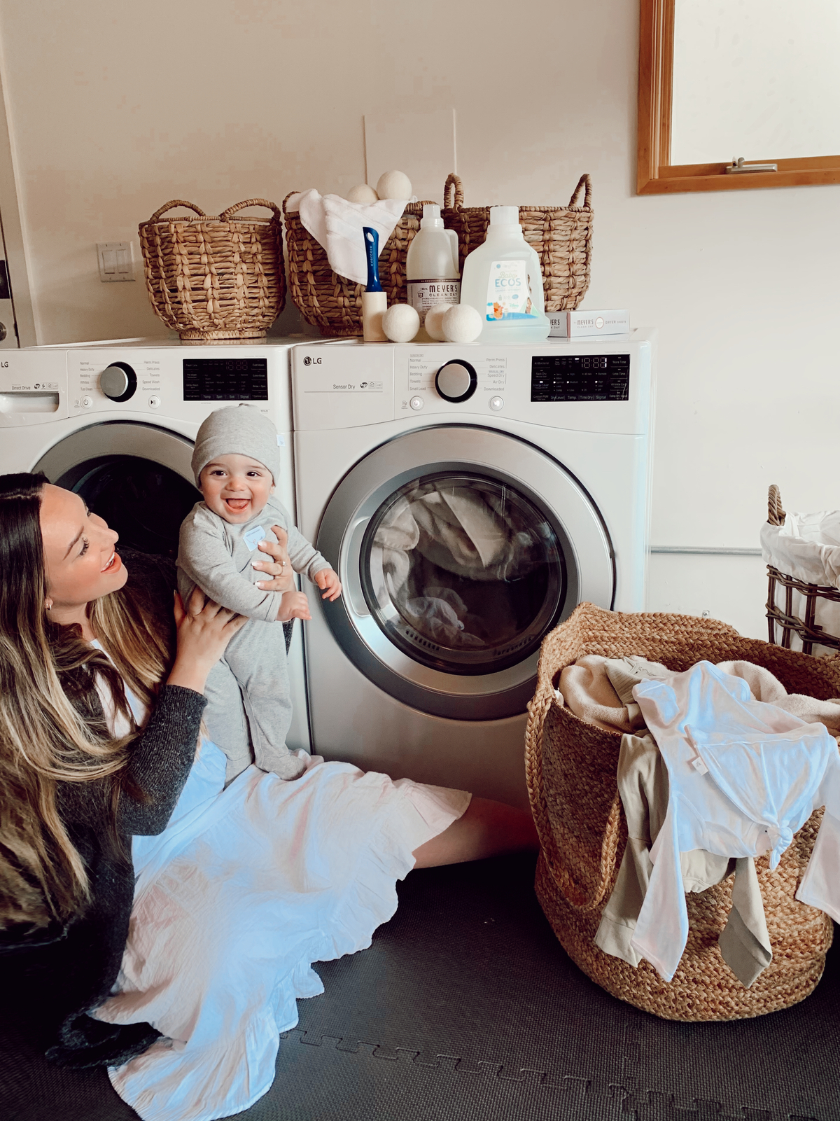 Laundry Storage by popular San Francisco lifestyle blog, Just Add Glam: image of a woman sitting on her laundry room floor with her baby next to some Bed Bath and Beyond Water Hyacinth Round Basket with Handles, Bed Bath and Beyond Bee & Willow™ Home Jute Laundry Hamper in Natural, Bed Bath and Beyond Baby ECOS Free & Clear Disney® 100-Ounce Laundry Detergent, Bed Bath and Beyond Woolzies® Wool Dryer Balls, Bed Bath and Beyond Evercare Lint Remover Bonus Pack, and Bed Bath and Beyond Wamsutta® Icon PimaCott® Bath Towel Collection.