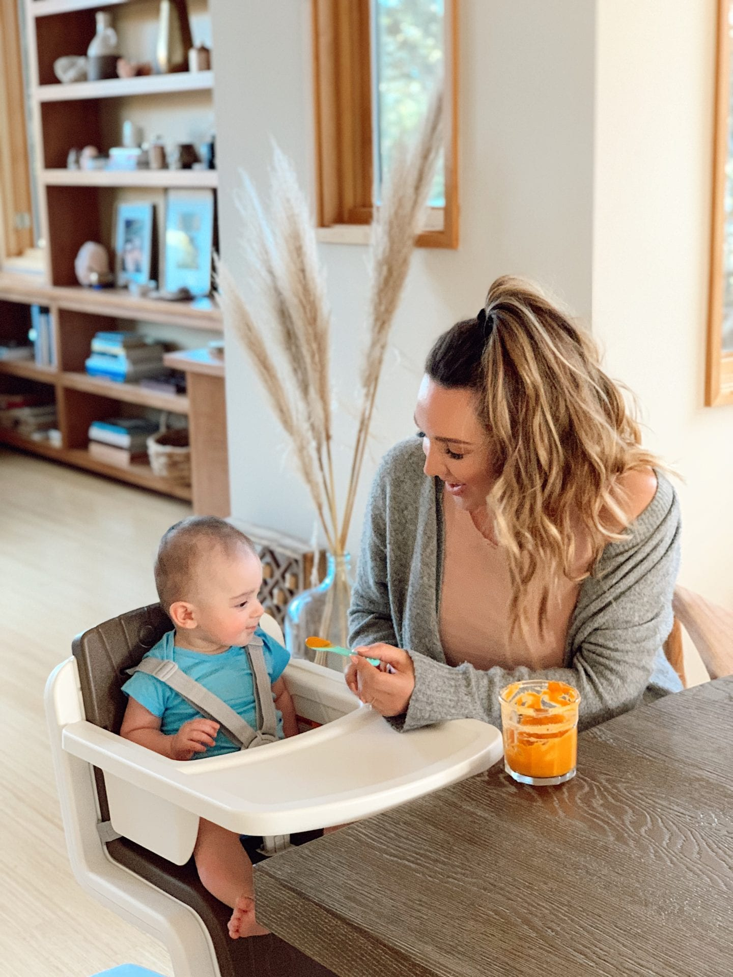 DIY baby food purees | Baby Food by popular San Francisco motherhood blog, Just Add Glam: image of a mom feeding her infant son some baby food as he sits in a Nuna ZAAZ high chair.