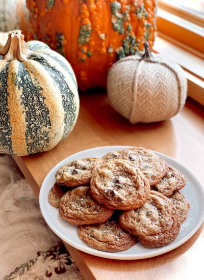 Pumpkin Flaky Salt Chocolate Chip Cookies | Pumpkin Chocolate Chip Cookies by popular San Francisco lifestyle blog, Just Add Glam: image of a plate of pumpkin chocolate chip cookies next to three pumpkins.