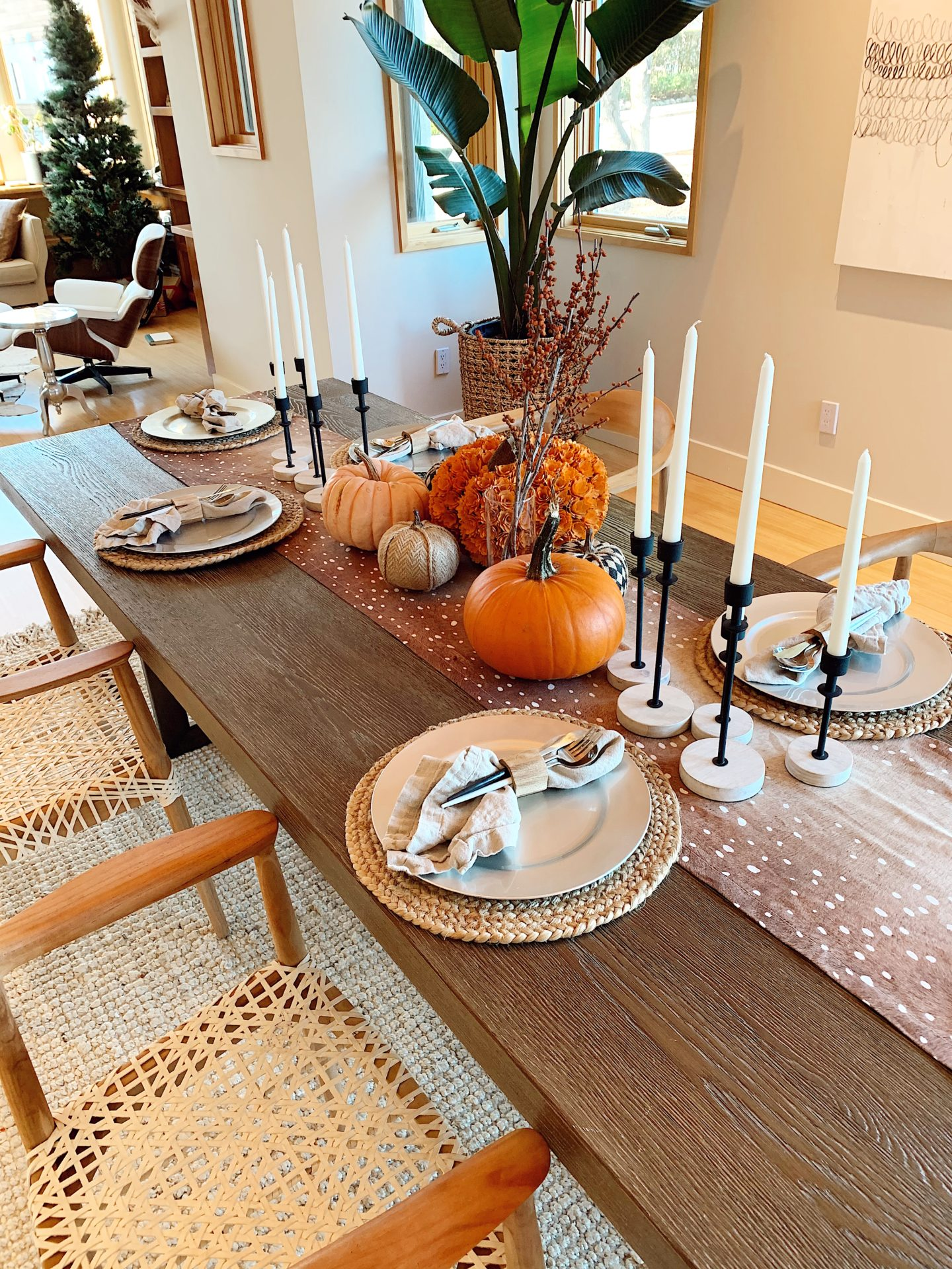 thanksgiving fall tablescape |Fall Tablescape by popular San Francisco life and style blog, Just Add Glam: image of a table decorated with an antelope print table runner, pumpkins, woven grass chargers, black candlestick holders, white candlesticks, cloth napkins with wooden napkin rings, and glass plates.