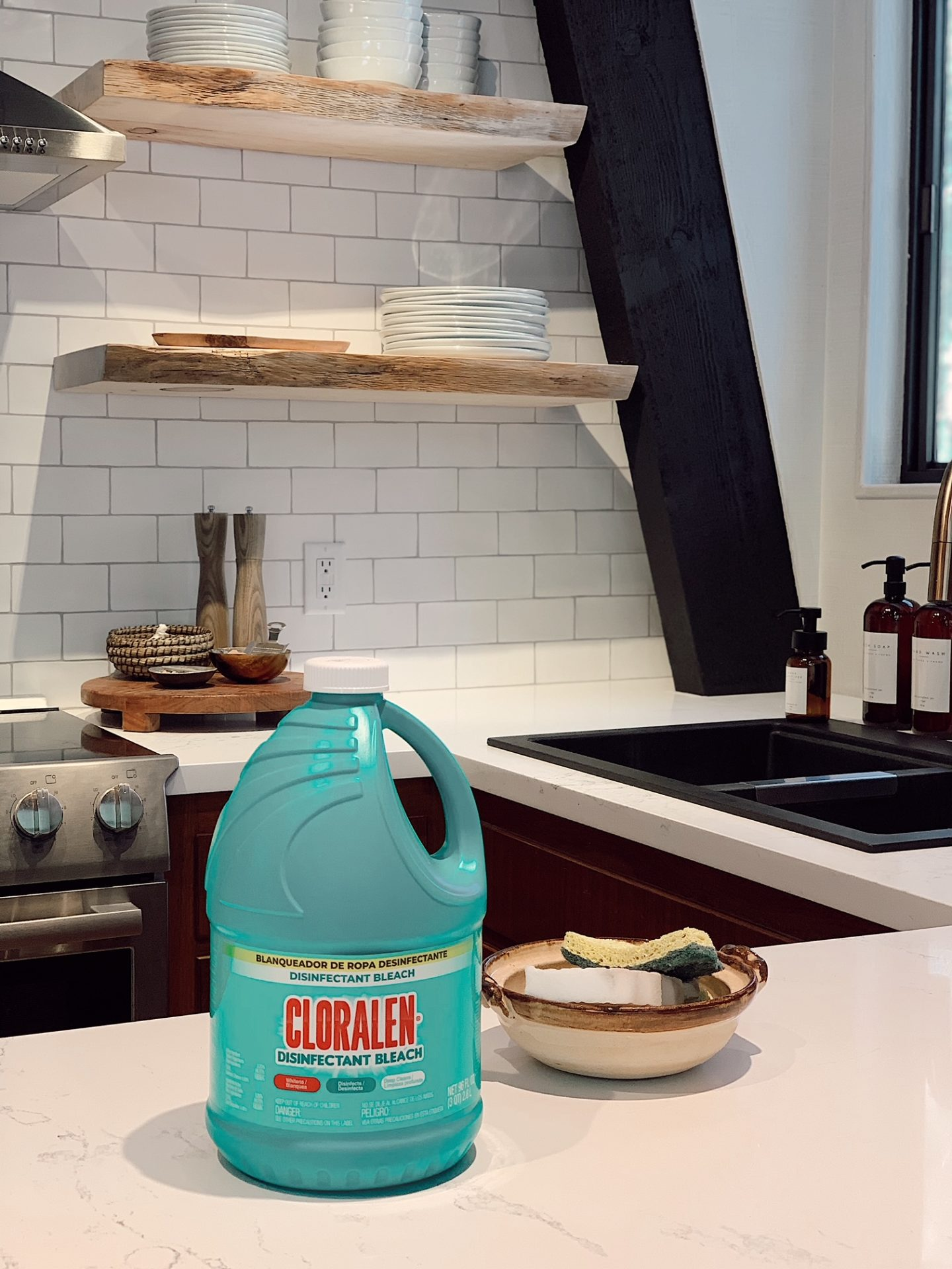 Cleaning with CLORALEN | Spring Cleaning Tips by popular San Francisco lifestyle blog, Just Add Glam: image of a bottle of Cloralen sitting on a kitchen counter next to a ceramic bowl filled with a sponge and magic eraser.