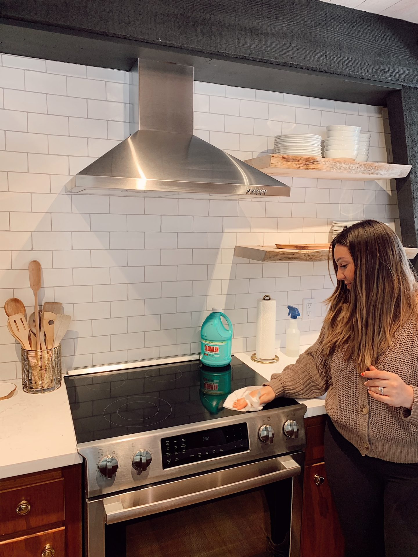 Cleaning with CLORALEN |Spring Cleaning Tips by popular San Francisco lifestyle blog, Just Add Glam: image of a woman holding a plastic spray bottle and wiping down her stove top.