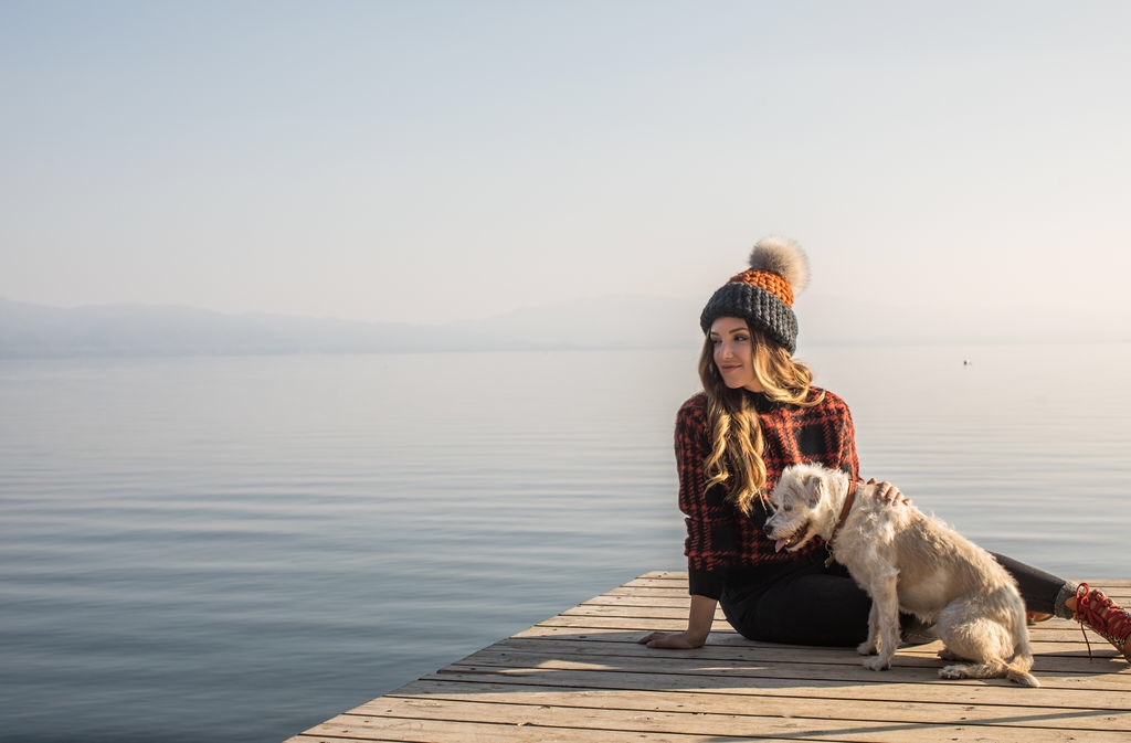 dog friendly beaches lake tahoe | Things To Do With Dogs by popular San Francisco lifestyle blog, Just Add Glam: image of a woman and her dog sitting on a dock at Lake Tahoe.